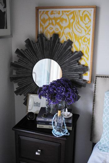nighstand grey starburst mirror purple flowers yellow ikat books