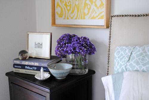 nightstand styling books purple flowers yellow ikat painting