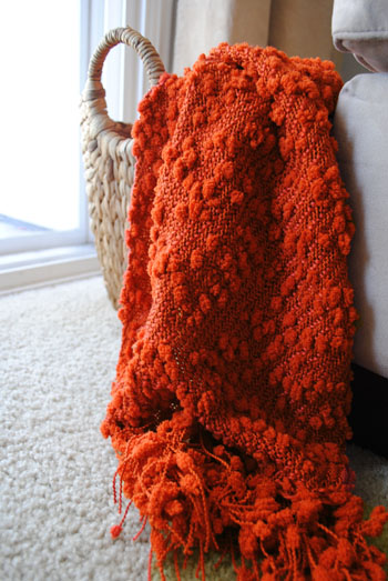 rust colored blanket in basket